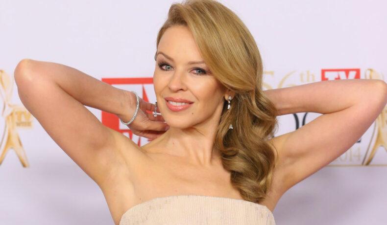 Kylie Minogue într-o rochie fără umeri, cu mâinile la ceafă și cu părul într-o parte zâmbind