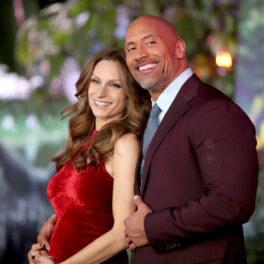 Dwayne Johnson ăn costum vișiniu, împreună cu soția lui, Lauren Hashian, într-o rochie roșie, la premiera filmului Jumanji 1