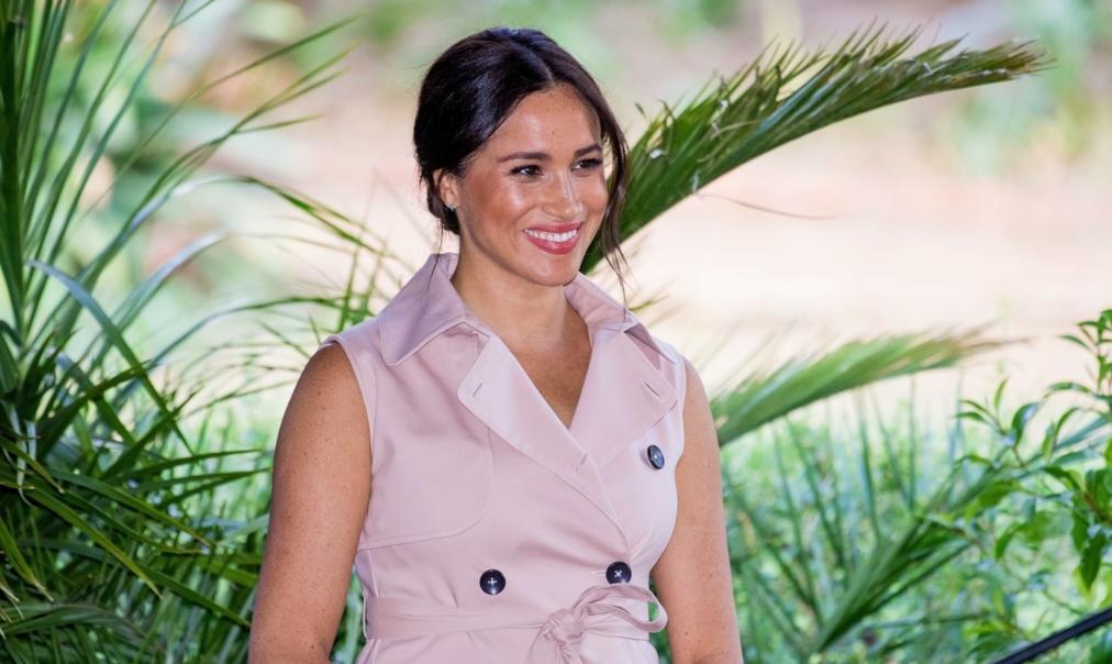 Meghan Markle zâmbește la un eveniment în timpul primei sarcini îmbrăcată cu o rochie crem cu nasturi și fără mâneci