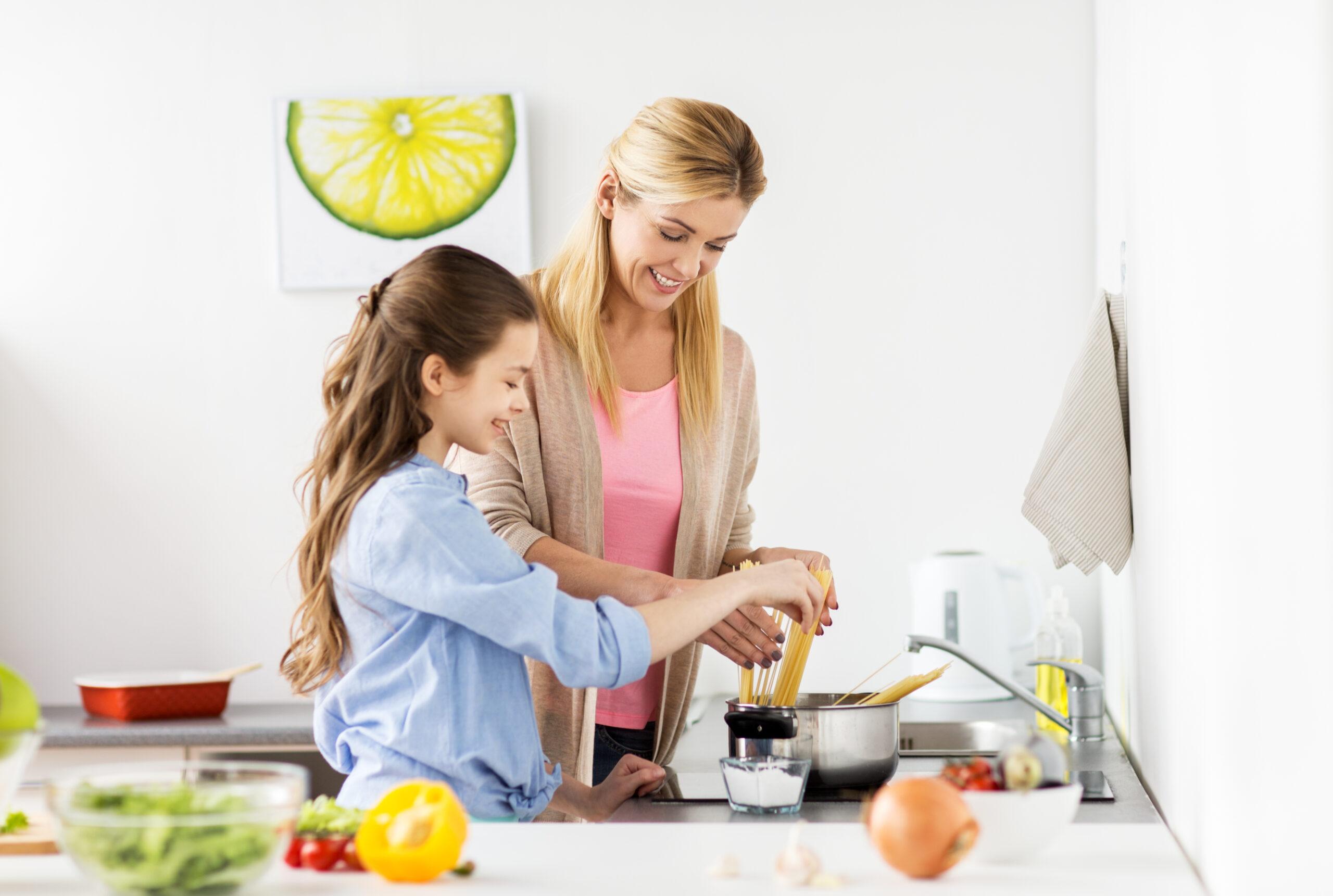 O mamă și fiica ei pregătesc paste împreună