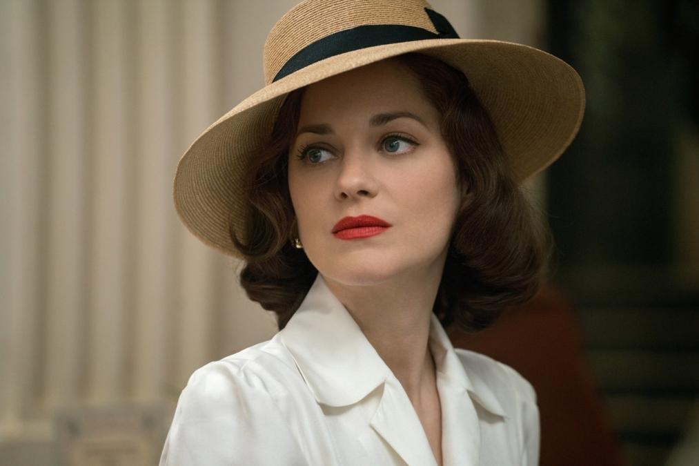 Portret cu Marion Cotillard îmbrăcată cu un sacou alb și o pălărie maro