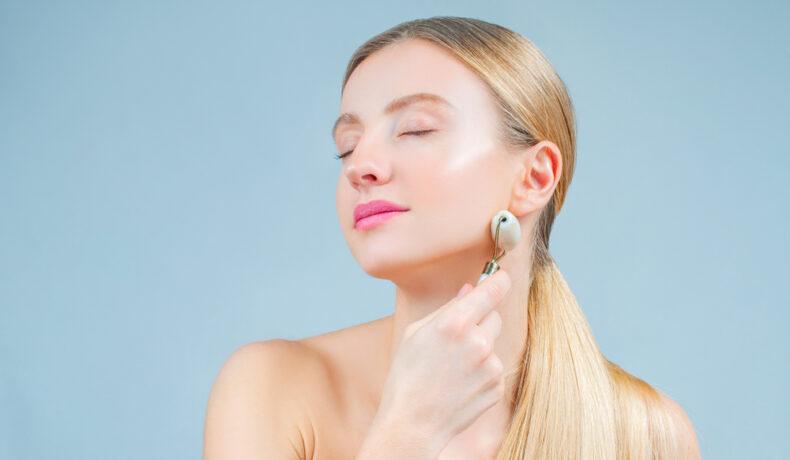 Femeie care își aplică masajul facial cu un roller de față