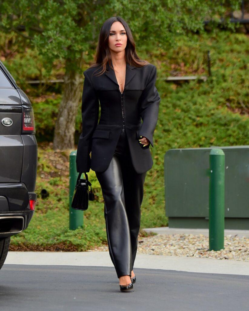 Megan Fox purtând un costum masculin negru cu pantaloni de piele și sacou