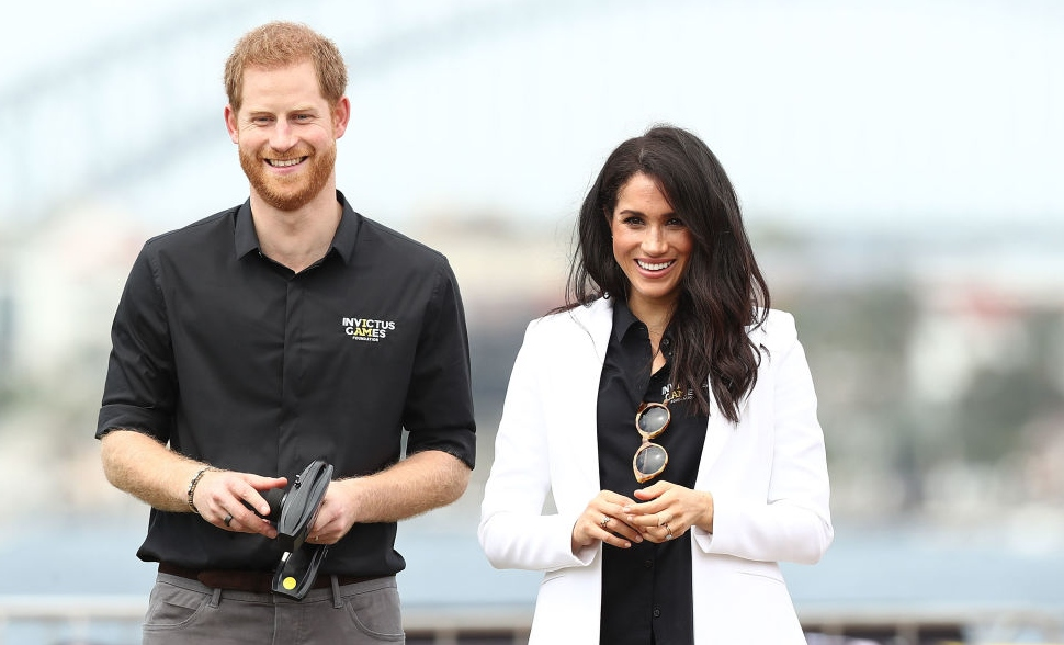 Meghan Markle și Prințul Harry zâmbesc în timp ce participă la un eveniment