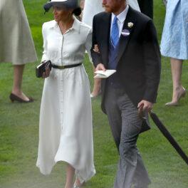 Meghan Markle îmbrăcată cu o rochie albă și o pălărie albă pe cap la brațul Prințului Harry îmbrăcat cu frac și joben