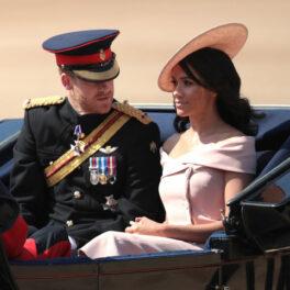 Meghan Markle în caleașcă alături de Prințul Harry îmbrăcată cu o rochie roz cu umerii goi și o pălărie roz