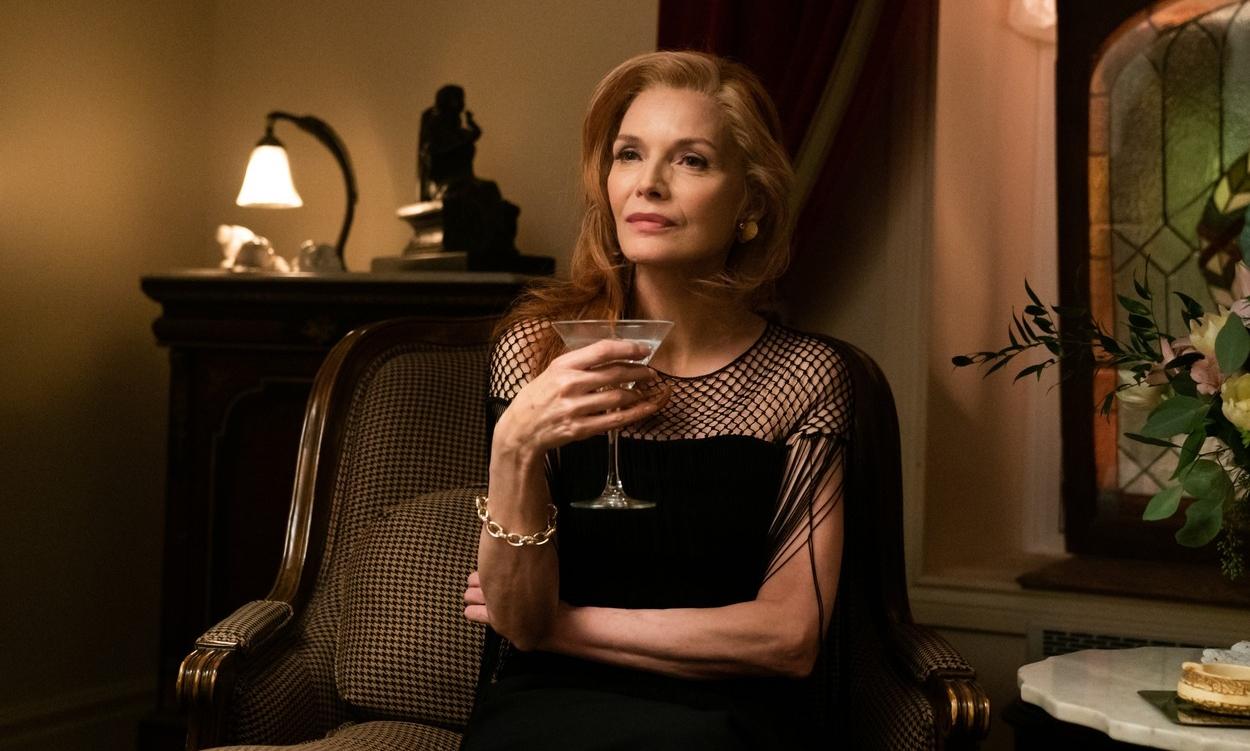Michelle Pfeiffer îmbrăcată într-o rochie neagră ține un pahat de martini în mână