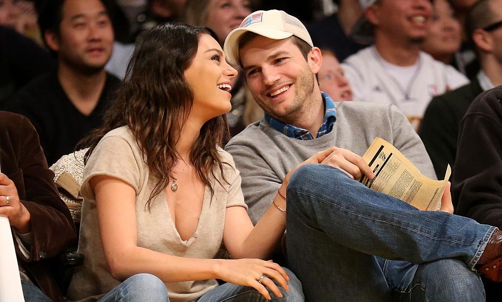 Mila Kunis și Ashton Kutcher râd la un meci de baschet