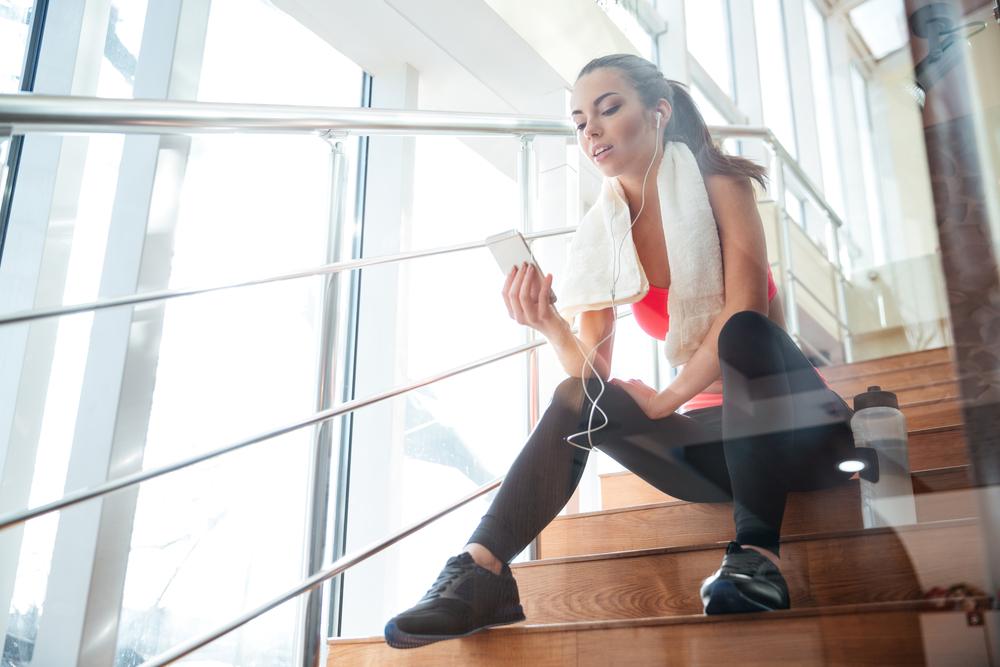 O femeie care a terminat o sesiune de antrenament și verifică pe telefon dacă a făcut cei 10 000 de pași zilnic