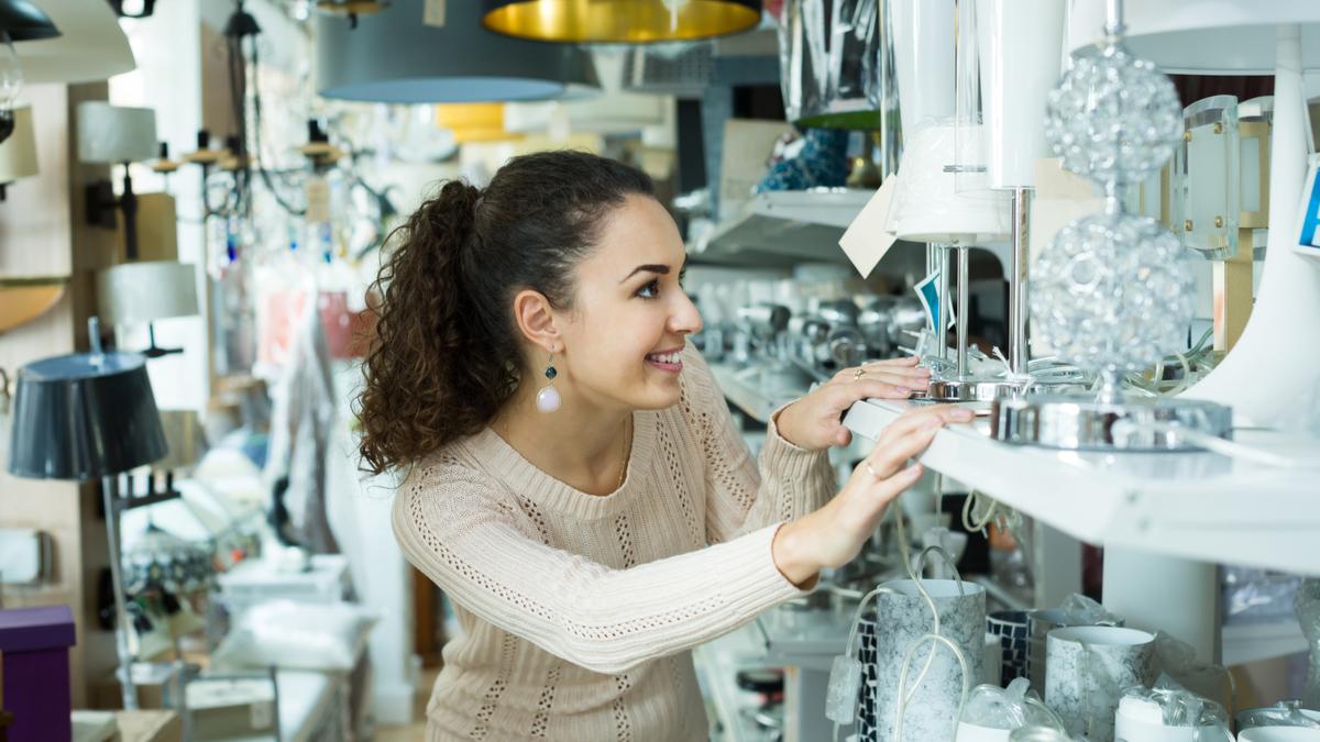 O femeie cu părul creț caută o lustră la raionul de lustre al unui magazin