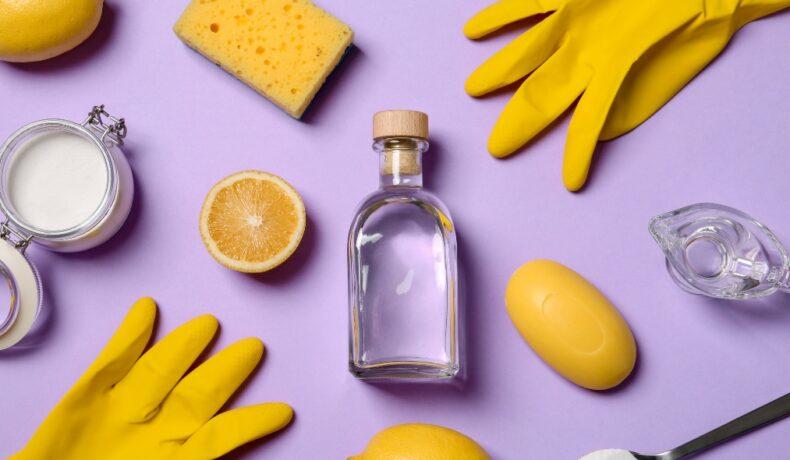 Mănuși de menaj, o sticlă de oțet, o lămâie și un burete de vase pe un fundal lila