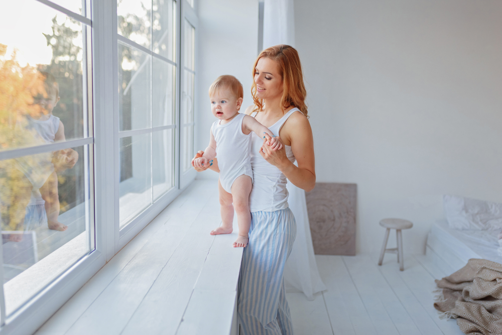 Un bebeluș pe pervazul geamului, în timp ce este susținut de mama sa