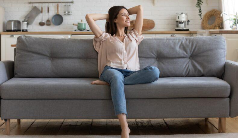 O femeie stă pe o canapea gri cu mâinile întinse la spate