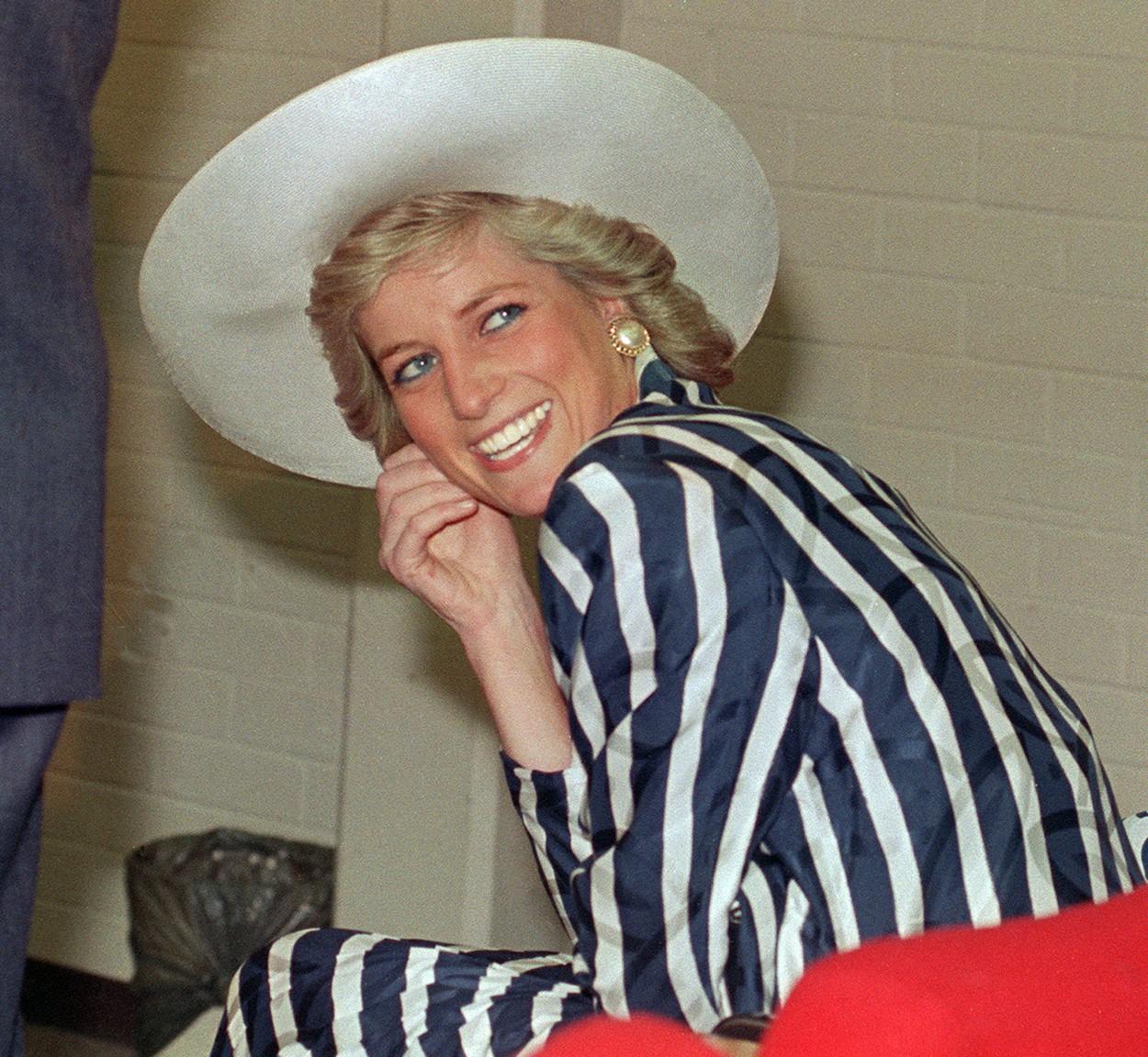 Prințesa Diana zâmbind larg cu o pălăria albă pe cap și cu într-o rochie în dungi albastre