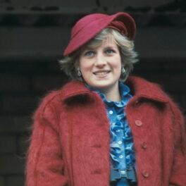 Prințesa Diana cu o pălărie burgundi pe cap, cu o bluză albastră și o haină cărămizie