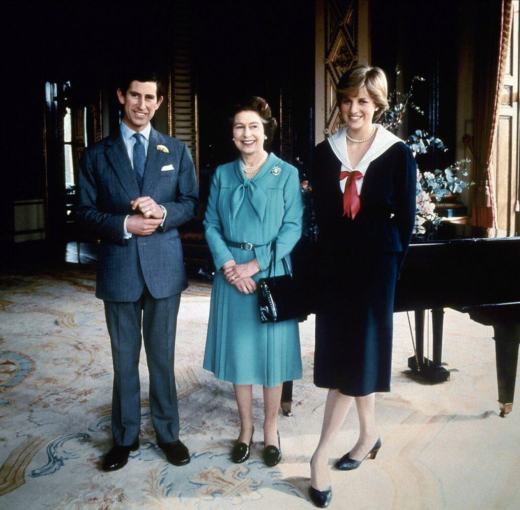 Prințesa Diana îmbrăcată într-o rochie neagră pozează într-o sufragerie alături de Regina Elisabeta îmbrăcată cu un costum albastru și de Prințul Charles îmbrăcat cu un costum gri