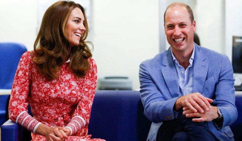 Prințul William și Kate Middleton sunt așezați pe o canapea și afișează zâmbete largi