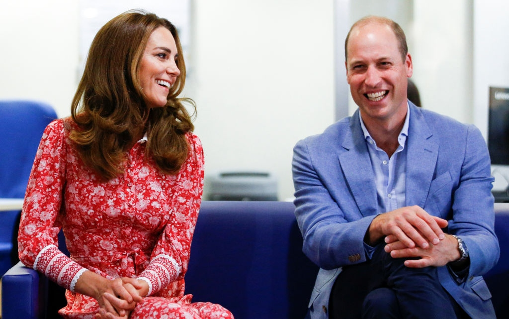 Prințul William și Kate Middleton sunt așezați pe o canapea și afișează zâmbete largi