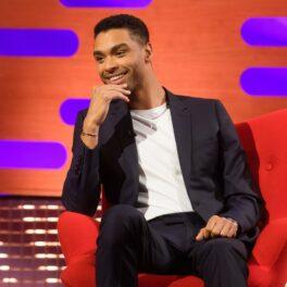 Regé-Jean Page stând pe un scaun roșu cu mâna la față în timp ce zâmbește