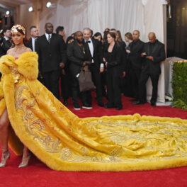 Rihanna într-o rochie cu trenă lungă, galbenă pe covorul roșu la Met Gala