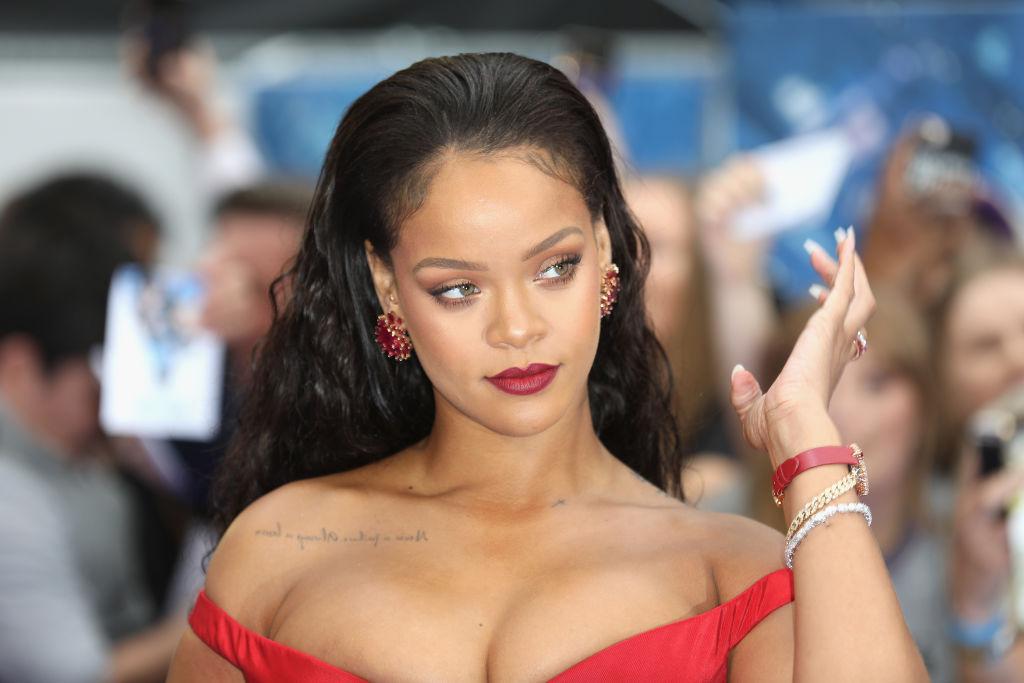 Rihanna într-o rochie roșie pe umeri prezentă pe covorul roșu