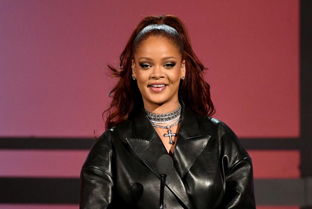 Rihanna într-o jachetă de piele neagră cu părul prins, vorbind pe scenă