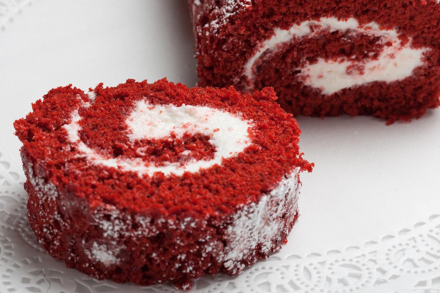 Secțiune dintr-o ruladă de sfeclă roșie cu cremă de brânză și ciocolată albă, gata de a fi servită
