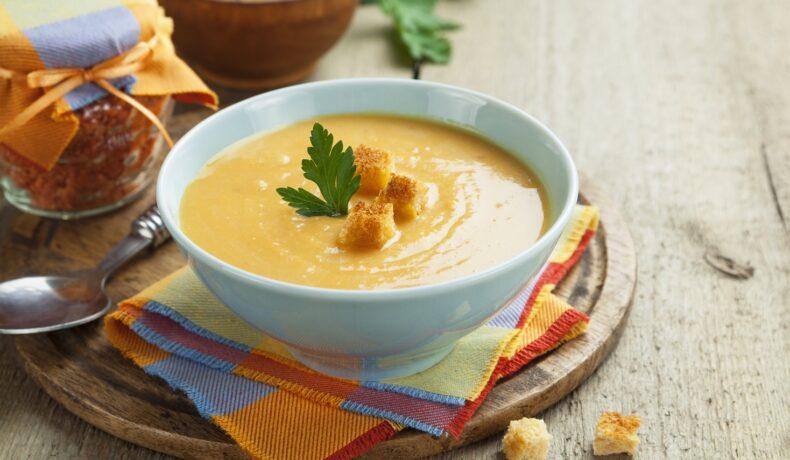 Un bol cu o porție de supă cremă de legume, servită cu crutoane
