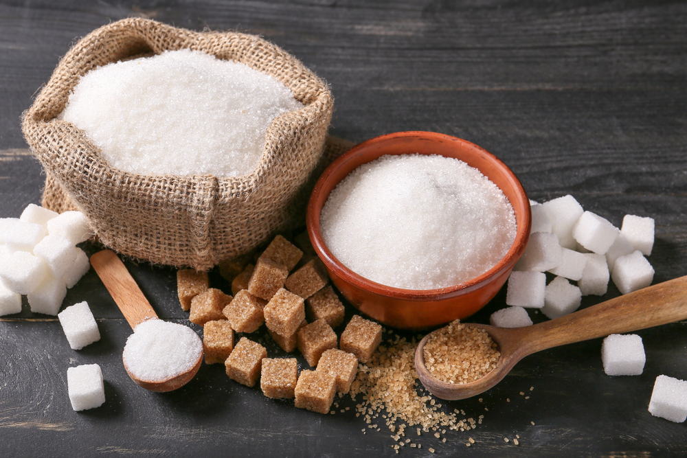 Zahărul granulat și zahărul brun depozitate în recipiente pe masă