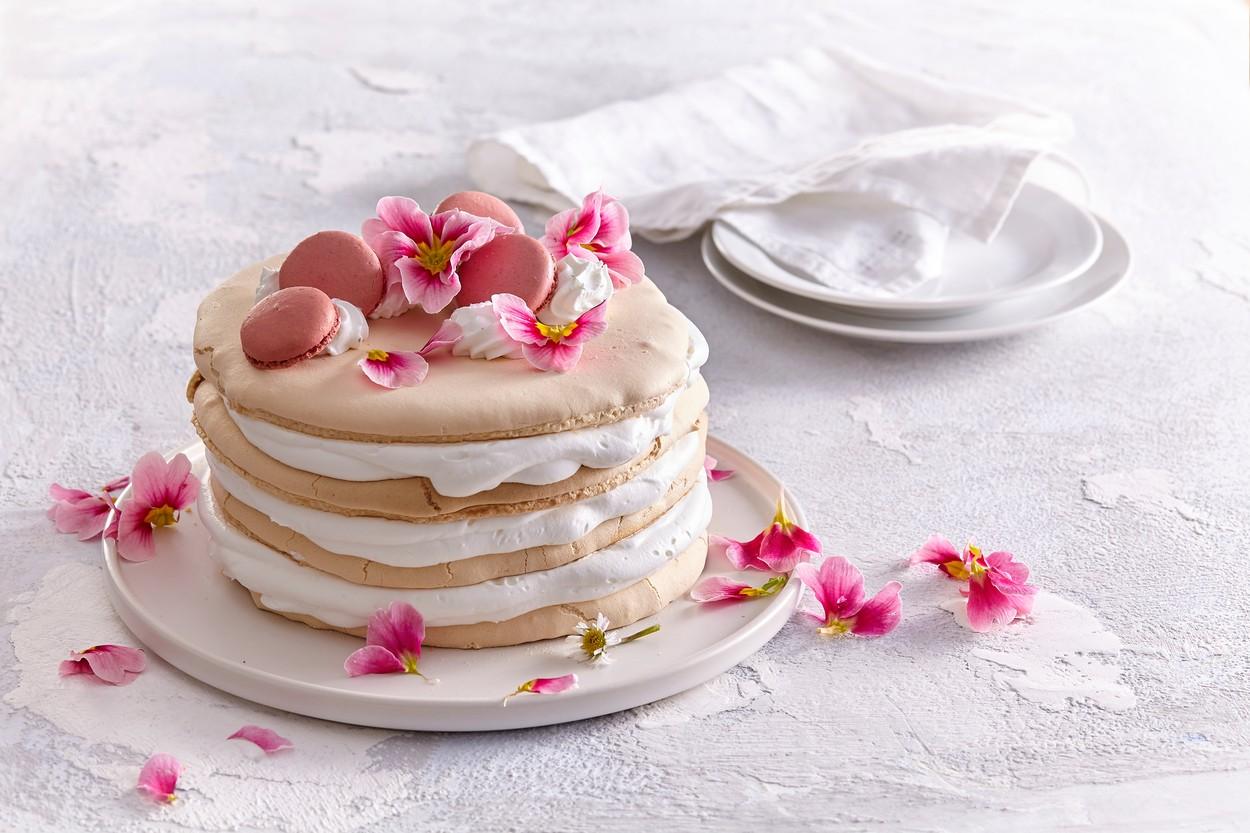 Tort pavlova decorat cu macarons și flori comestibile