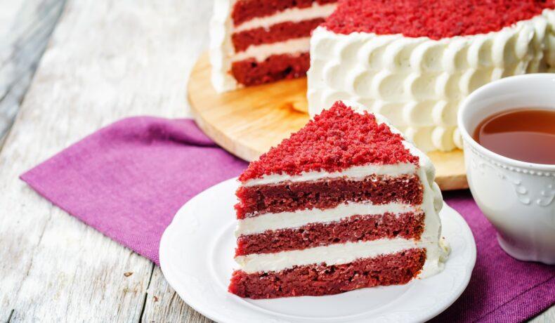 Secțiune dintr-un Red Velvet Cake pe un platou alb, gata de a fi servită de ziua îndrăgostiților