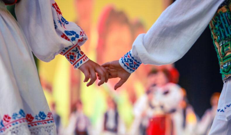 Un băiat și o fată îmbrăcați în costume populare se țin de mână
