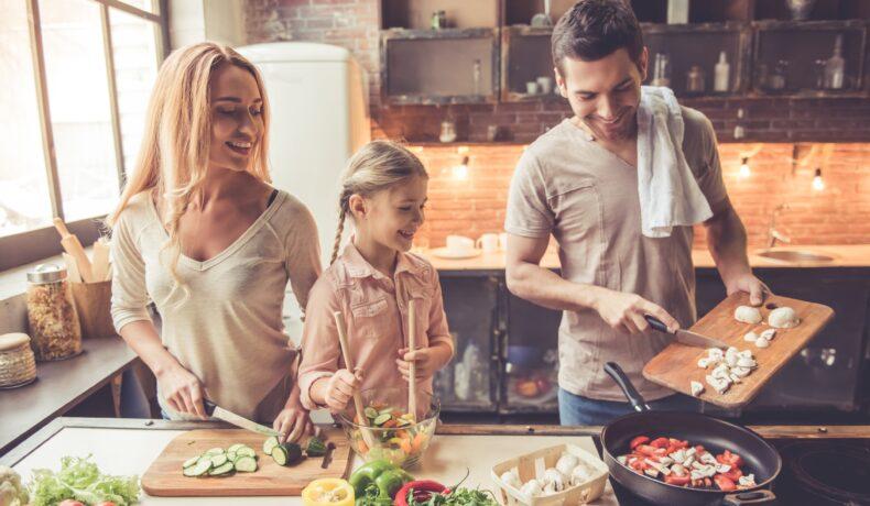 Un bărbat, o femeie și o fetiță gătesc împreună