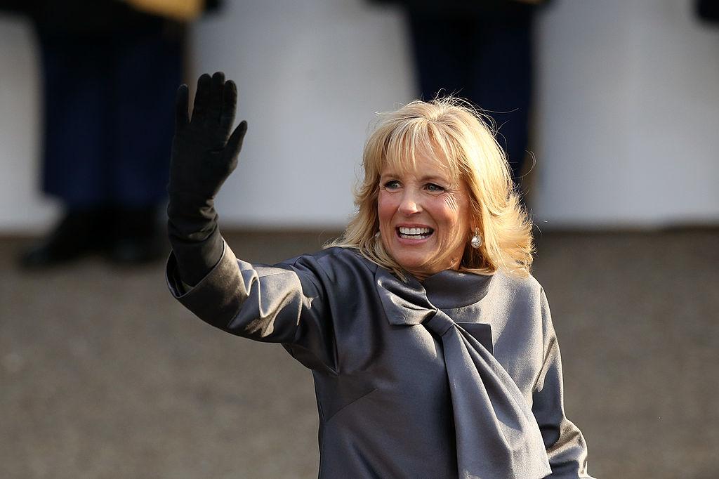 Jill Biden salută mulțimea îmbrăcată într-un palton gri cu fundă și mănuși negre