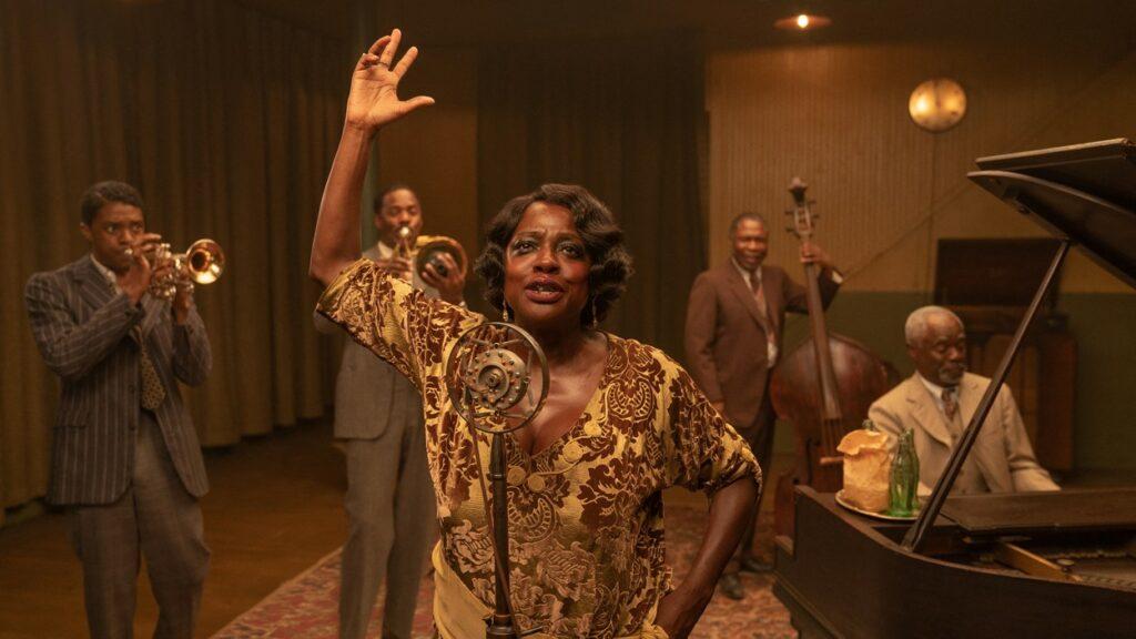 Viola Davis în rolul lui Ma Rainey cântă la un microfon în timp ce este îmbrăcată într-un costum de epocă