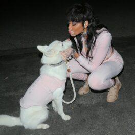 Winnie Harlow îmbrăcată cu un training roz alături de câinele ei îmbrăcat cu o haină roz
