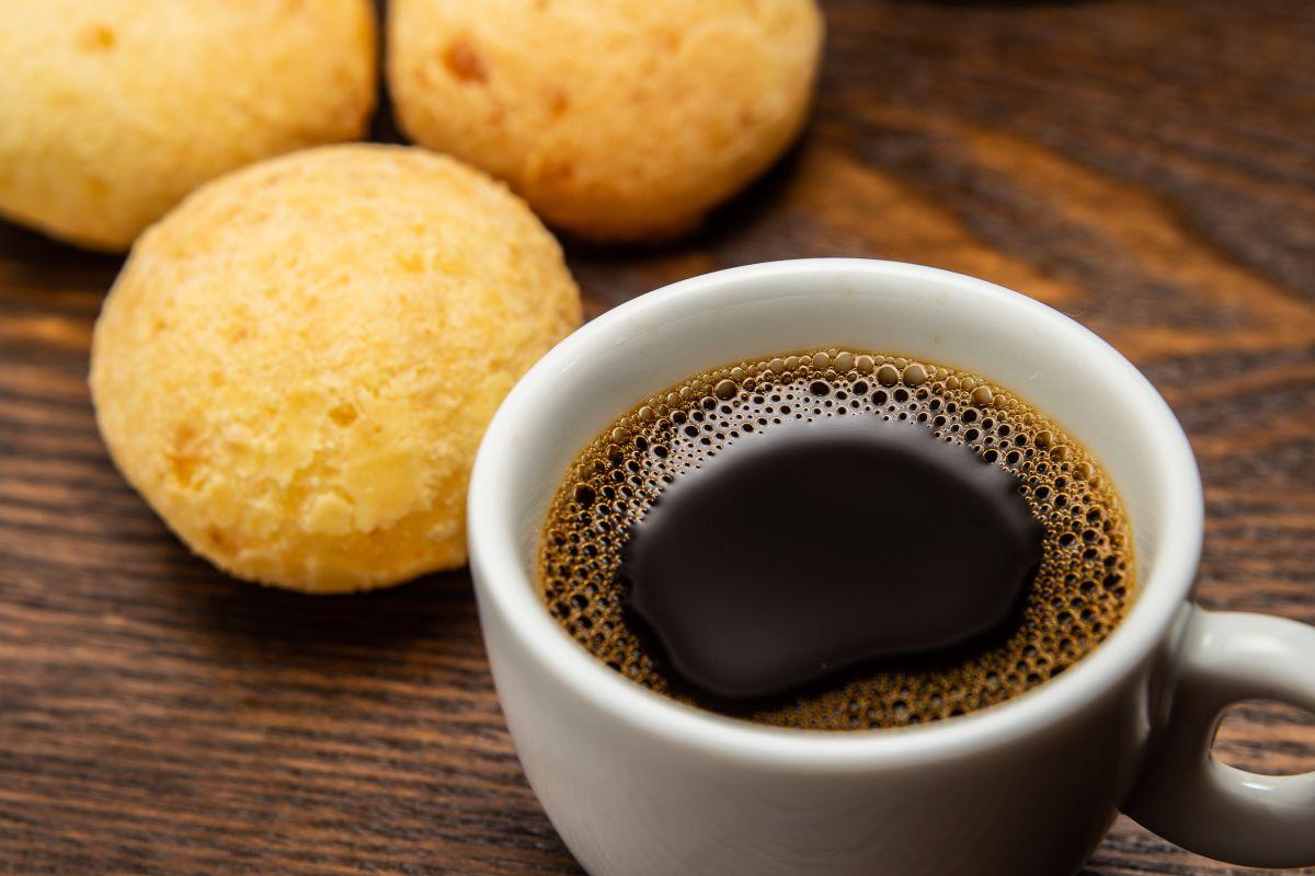 O ceașcă de cafea, alături de niște biscuiți, așezați pe o masă