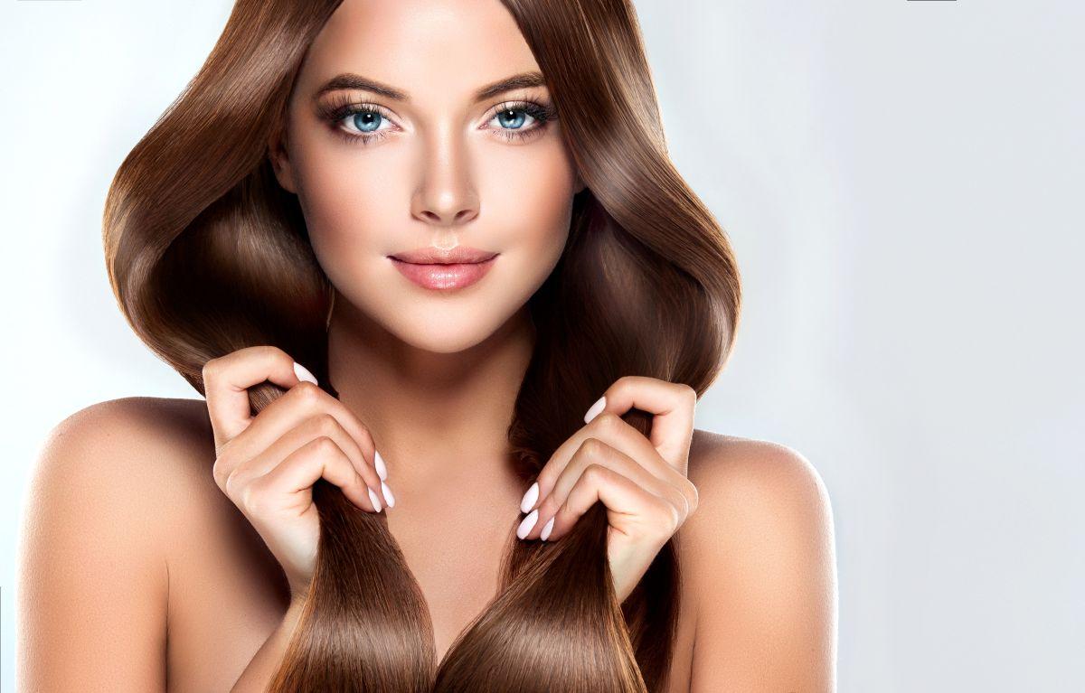 Fată care își ține în palme părul mătăsos și strălucitor
