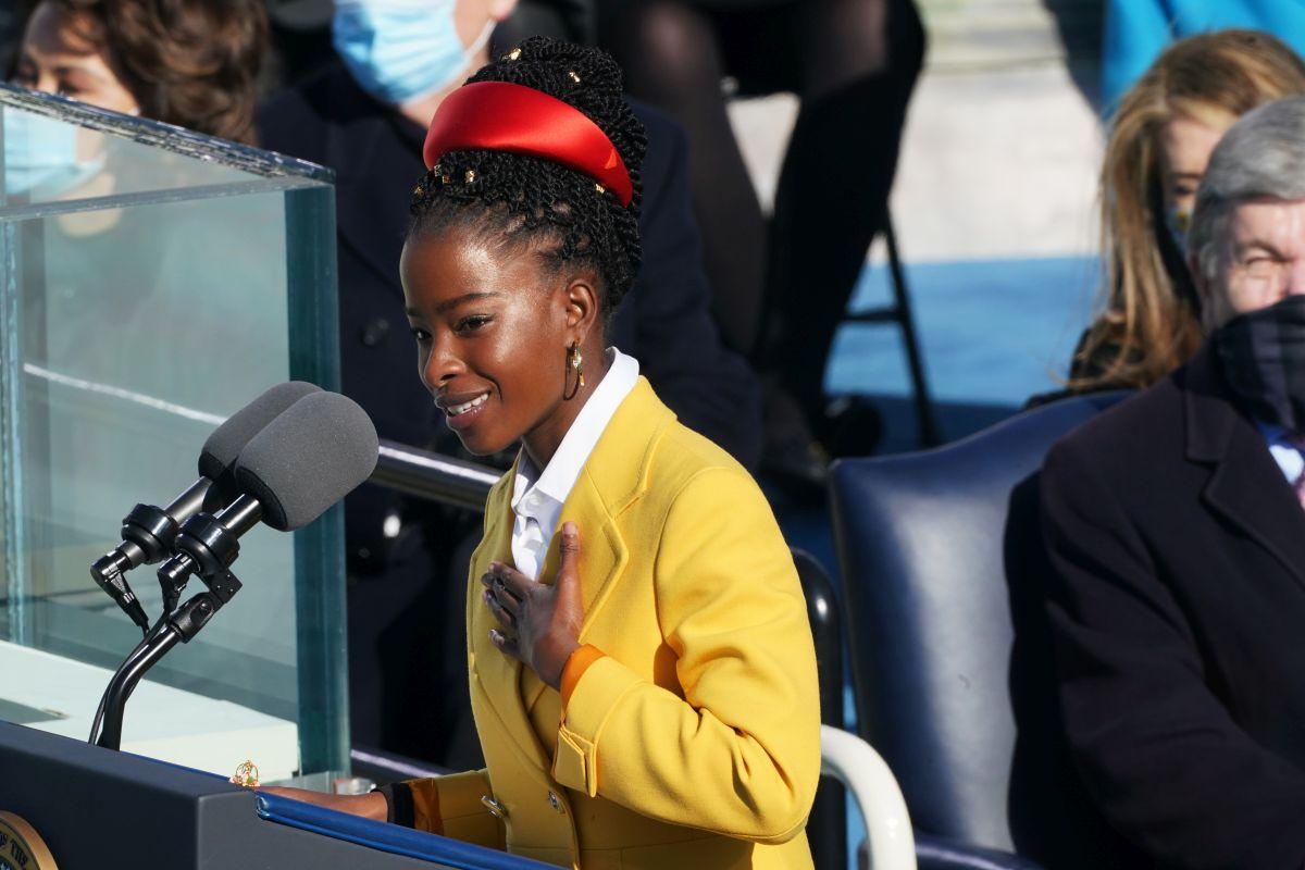 Amanda Gorman, îmbrăcată cu un palton de culoare galbenă, cu părul strâns cu un accesoriu de culoare roșie, susține un discurs în cadrul ceremoniei de investire a lui Joe Biden, președintele SUA.