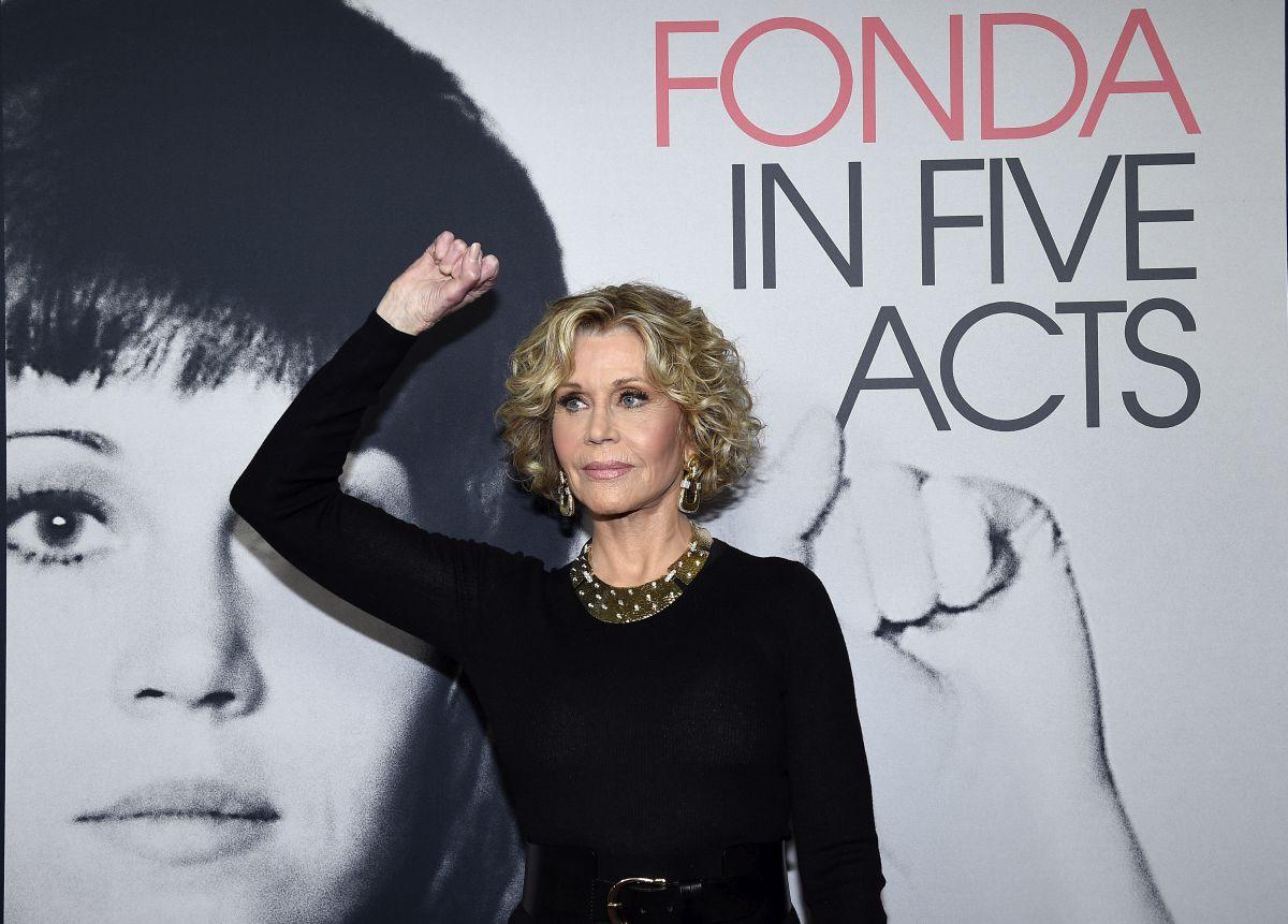 Jane Fonda, într-o rochie neagră, pozează cu pumnul ridicat