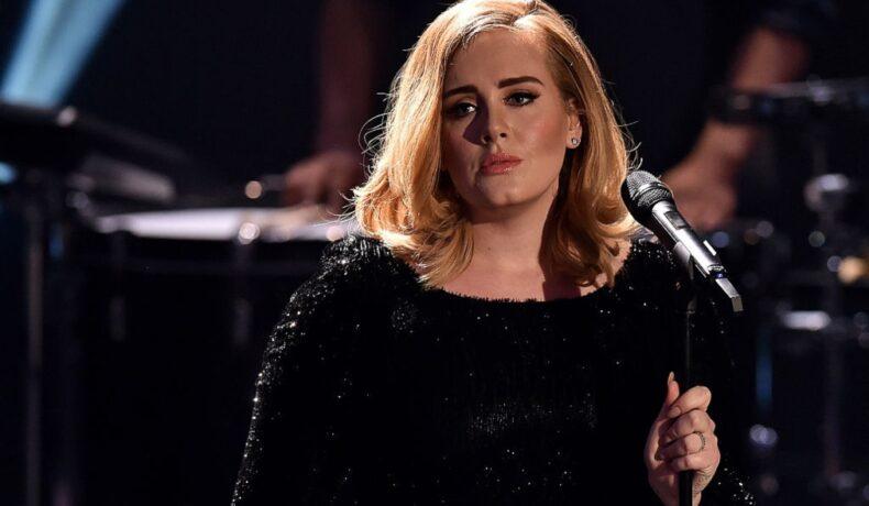 Adele pe scenă cu microfonul în mână îmbrăcată cu o eochie neagră sclipitoare