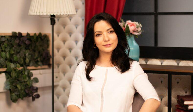 Anca Diniciu, îmbărăcată cu o bluză albă, cu părul desfăcut, fotografiată în timpul unui interviu pentru CaTine.ro