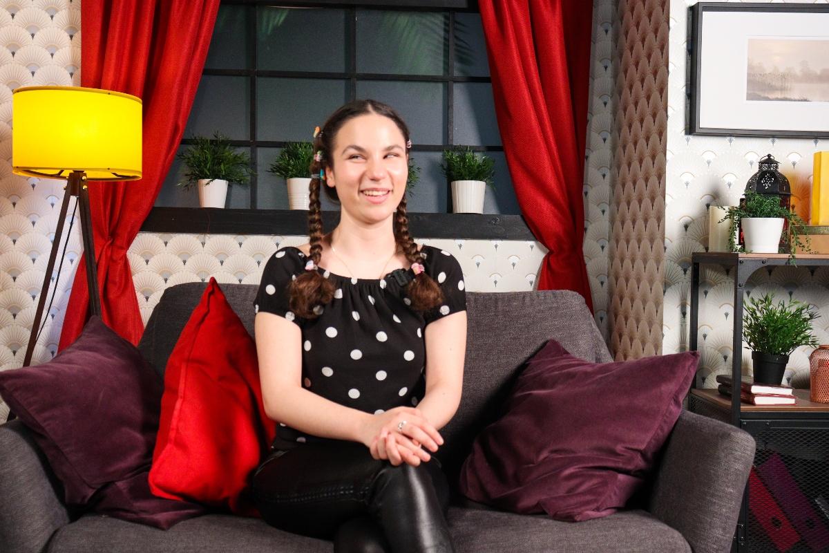 Andrada Precup, pe canapeaua unui studio de filmări, suprinsă în timp ce zâmbește în cadrul unui interviu
