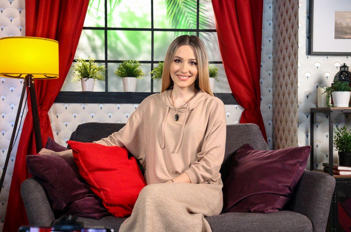Camelia Bălțoi, într-un studio, îmbrăcată elegant, cu zâmbetul pe buze