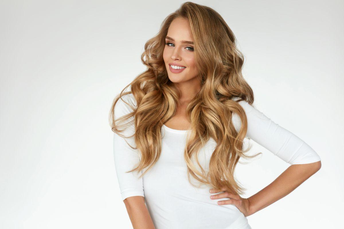 O femeie blondă, zâmbitoare, cu un păr lung și îngrijit