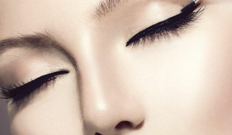 O femeie cu buze roșii stă cu ochii închiși pentru ca linia de tuș să fie vizibilă.