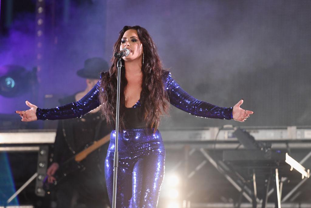 Demi Lovato pe scenă îmbrăcată cu o salopetă mulată strălucitoare și albastră cu decolteu adânc
