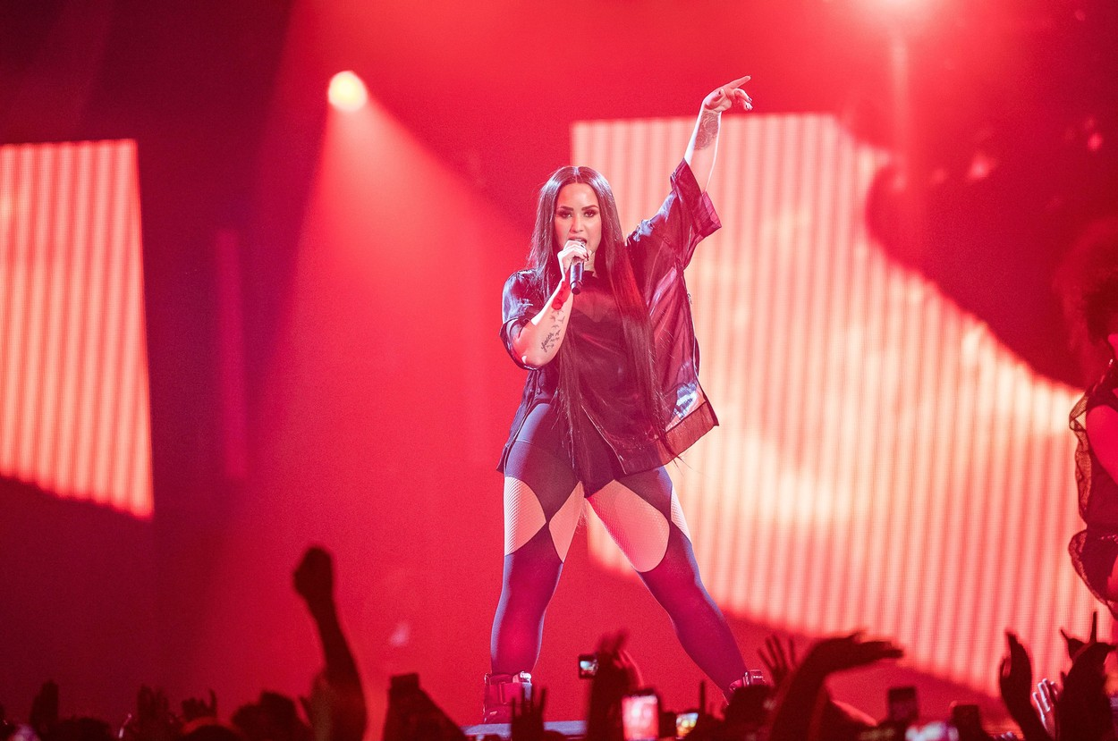 Demi Lovato pe scenă îmbrăcată cu o ereche de colanți negri decupați