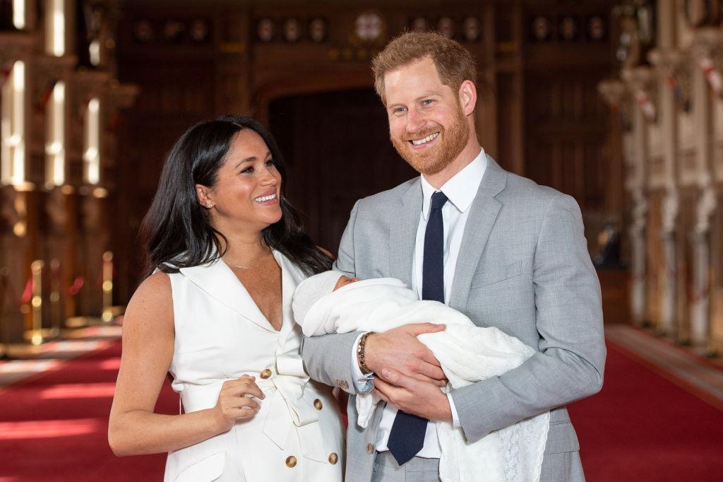 Prințul Harry și Meghan Markle zâmbesc în timp ce îl țin în brațe pe nou-născutul Archie
