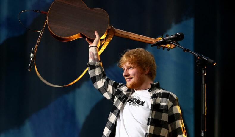 Ed Sheeran, fotografiat în timp ce își ridică chitara pentru a saluta fanii în timpul unui concert